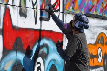 Mitchell Schorr spray painting a mural