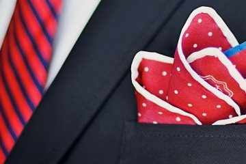 Men's suit with red and white handkerchief and red with blue stripes tie