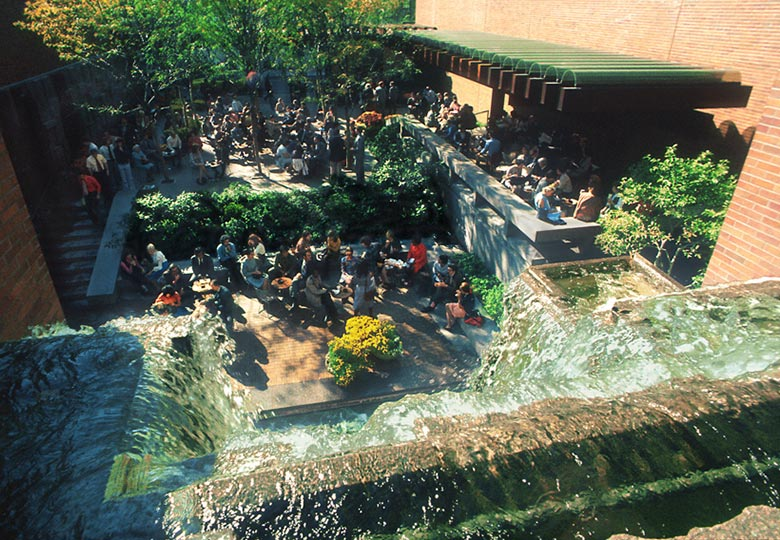 Greenacre park with waterfall fountain and people sitting