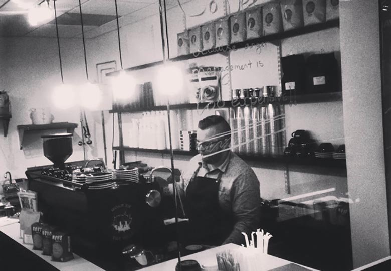 Black and white image of a barista making coffee
