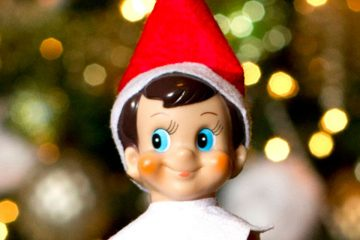 Elf on the Shelf face with Christmas tree in the background