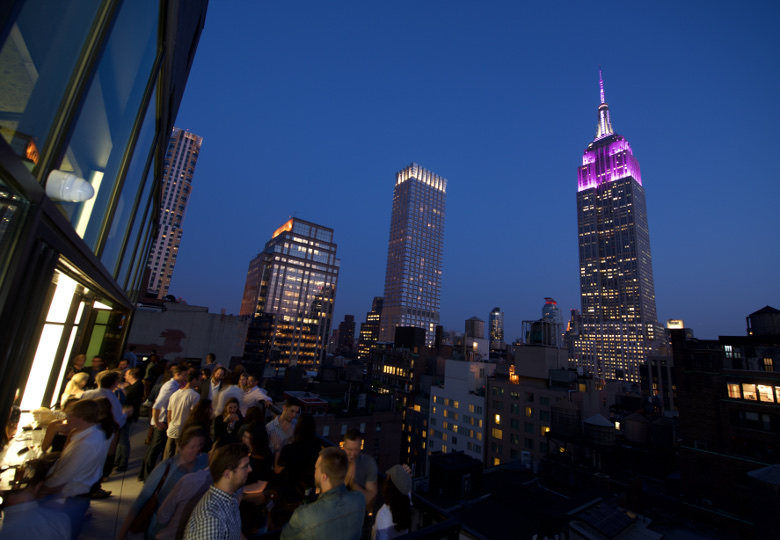 Spyglass Rooftop Bar at Archer Hotel New York Looking Out Over The Empire State Building at Dusk