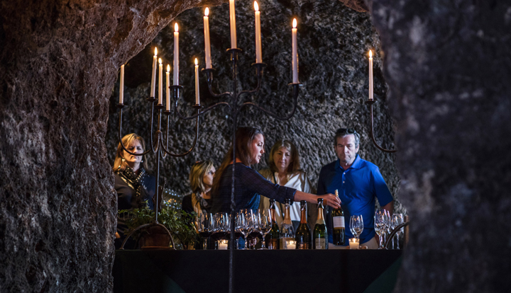 A wine tasting in a cave with a host pouring wine for guests and a rustic candelabra in the foreground