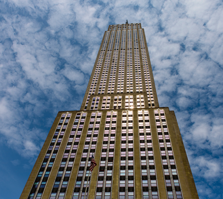 Looking up at the Empire State Building with Clouds and blue sky — Photo courtesy of Zvika Kuperman from Pexels