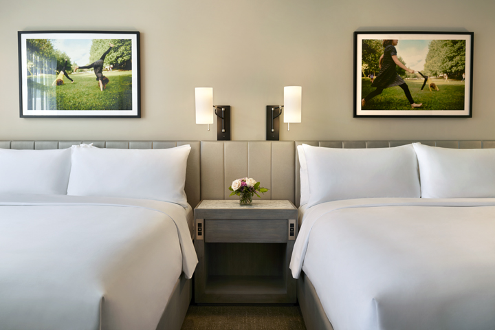 Two king beds with large photography above the headboards