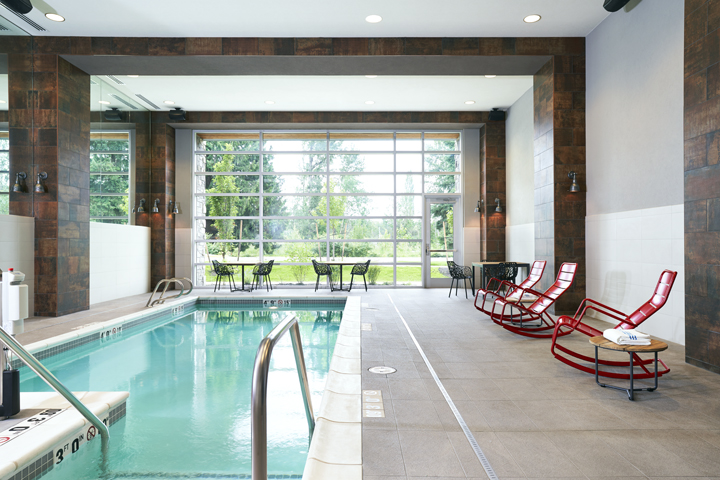 Archer's pool with tables and black chairs plus red rockers and a floor-to-ceiling view of trees