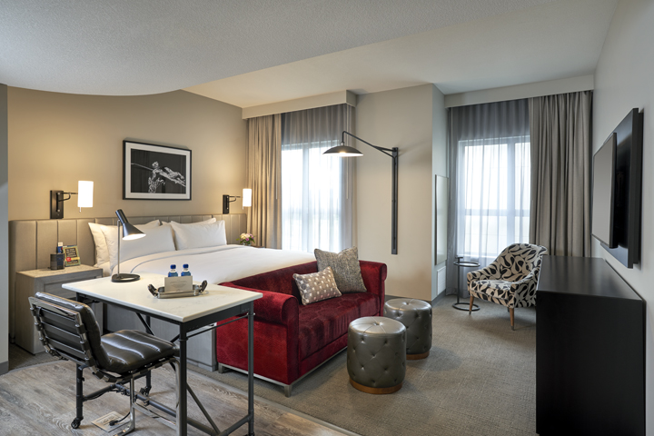 Deluxe King Studio with a king-size bed with white linens, a red sofa, a side chair, a raised table and chair and windows