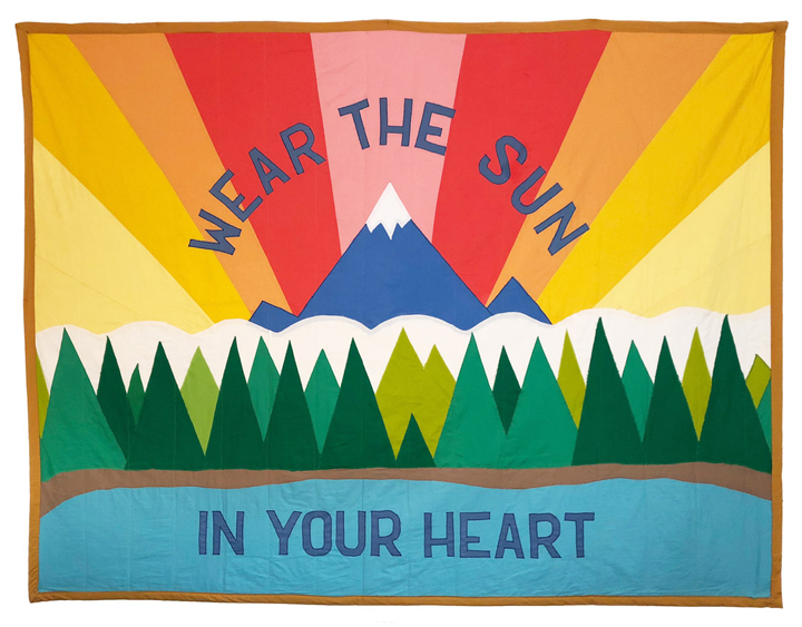 "Quilt that depicts a body of water, trees, snow, a snow-capped mountain and sun rays, with the message ""WEAR THE SUN IN YOUR HEART"""