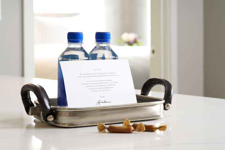 Two bottles of water, salted caramels and a welcome note on a metal tray with leather handles