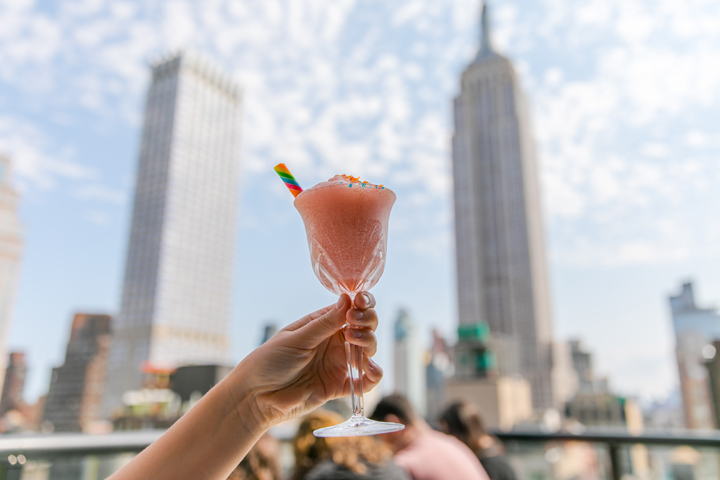 A pink Froze cocktail being held up with the Empire State Building and blue sky in the background