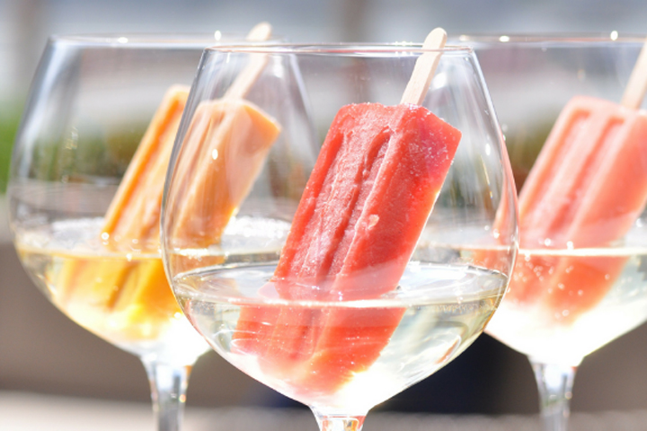 Three fruit-flavored ice pops resting in three wine glasses filled with Prosecco