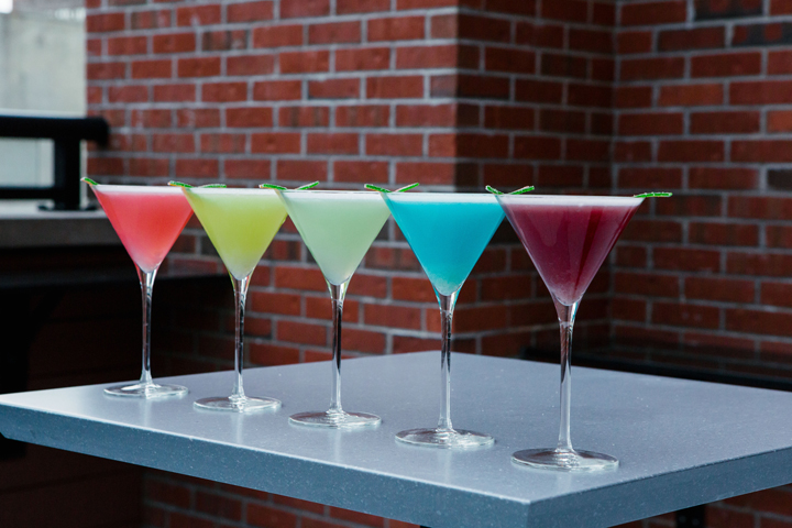 Five martini glasses in a row on a table, each filled with a single-color martini, and a brick wall in the background