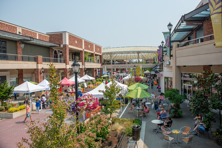 Redmond Town Center — the open-air Center Street Plaza with shops lining the wide walkway, vendor canopies and dining tables with umbrellas