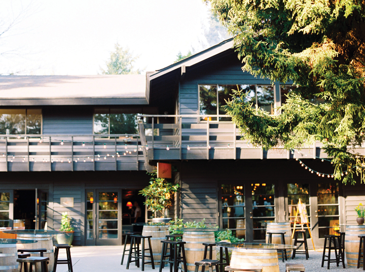 Exterior of JM Cellars — a two-story building with an outdoor walkway, plus wine barrels and stools set up on the ground-level patio.