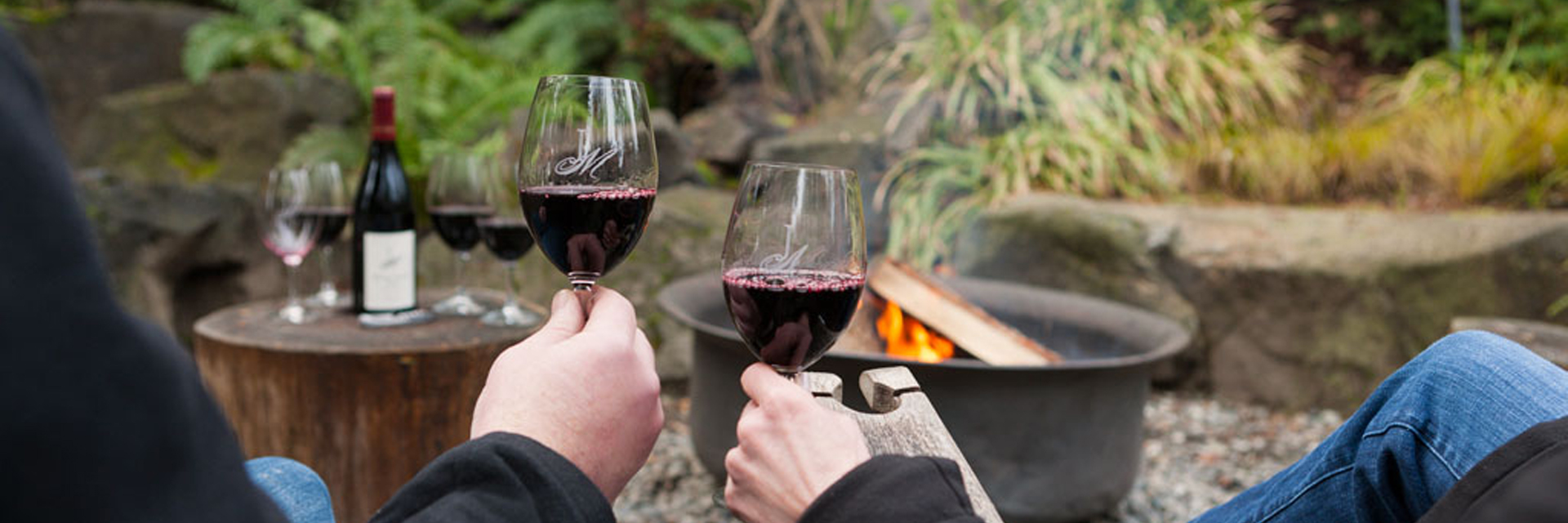 A man and a woman's hands each holding a glass of red wine while sitting in front of a firepit, with more wine glasses and a wine bottle sit atop a log table