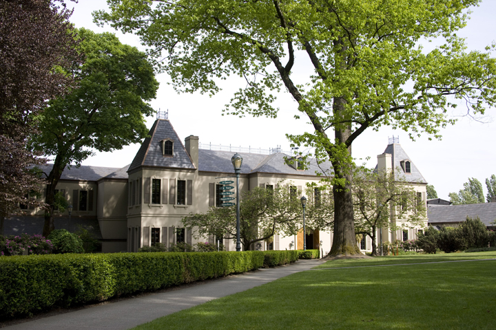 Exterior daytime view of Chateau St. Michelle, a grand building surrounded by trees and green lawn