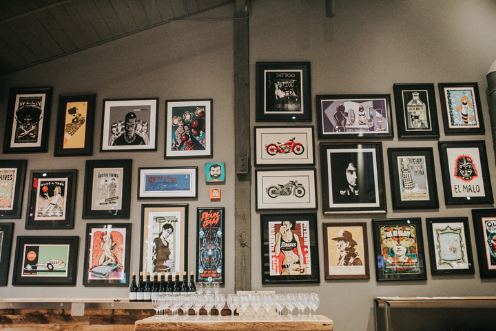 A wall of artwork behind a collection of wine glasses on a table.