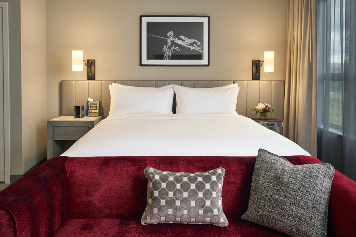 A king-size bed, red sofa and photograph of Jimi Hendrix in a hotel room