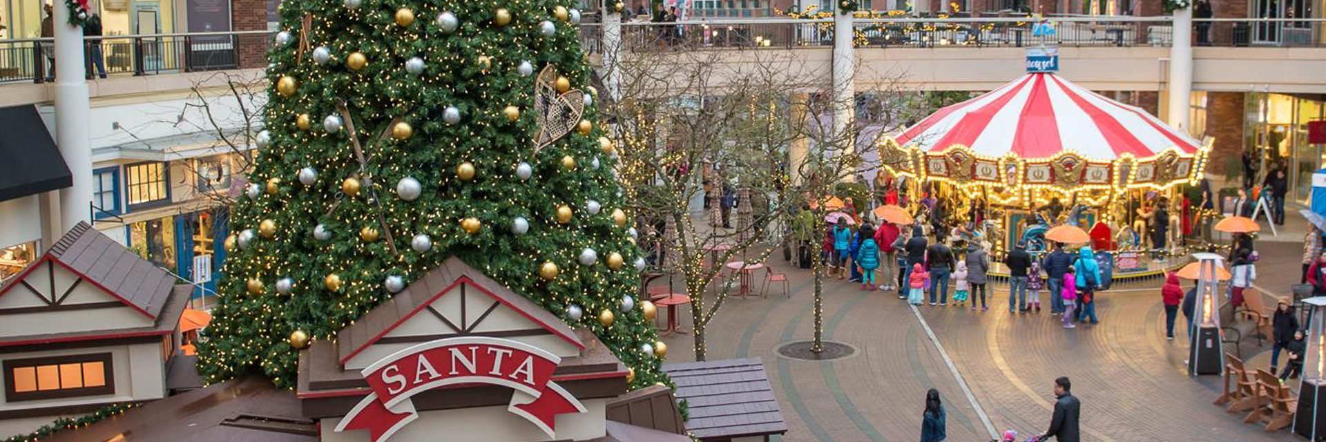 A large Christmas tree, Santa's Workshop and a carousel at an outdoor shopping center