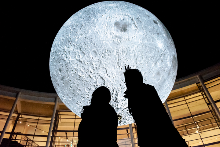 Silhouette of two people looking at a large moon art outside a building