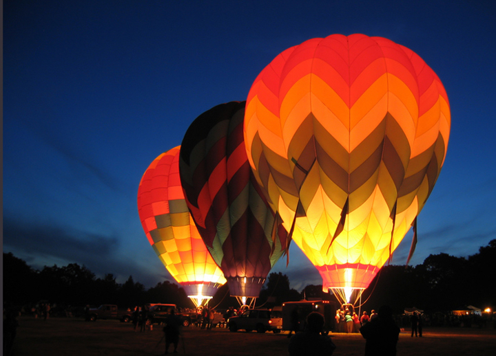 Three tethered balloons lit up at night