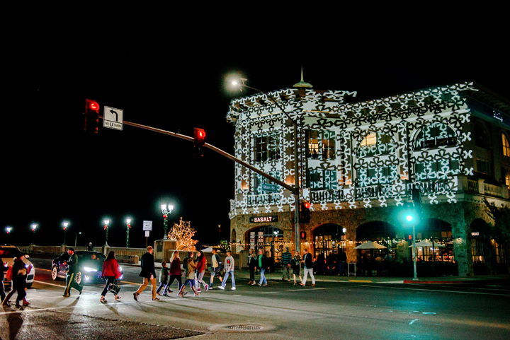 A group of people crossing the street in front of Basalt in the Riverfront building at night