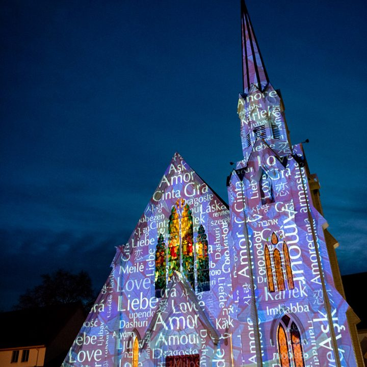Word art projected onto a church at night