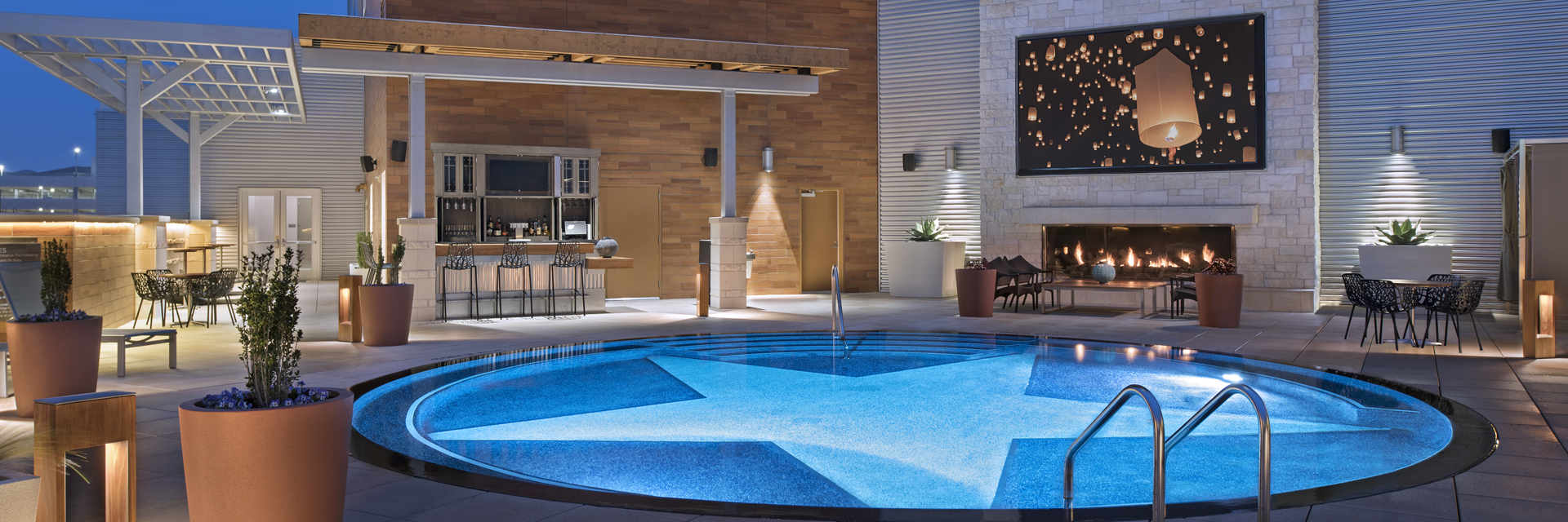 Nighttime view of the pool patio at Archer Hotel Austin — star-bottom splash pool with lounge seating, outside bar, fireplace and oversized TV on a limestone wall.