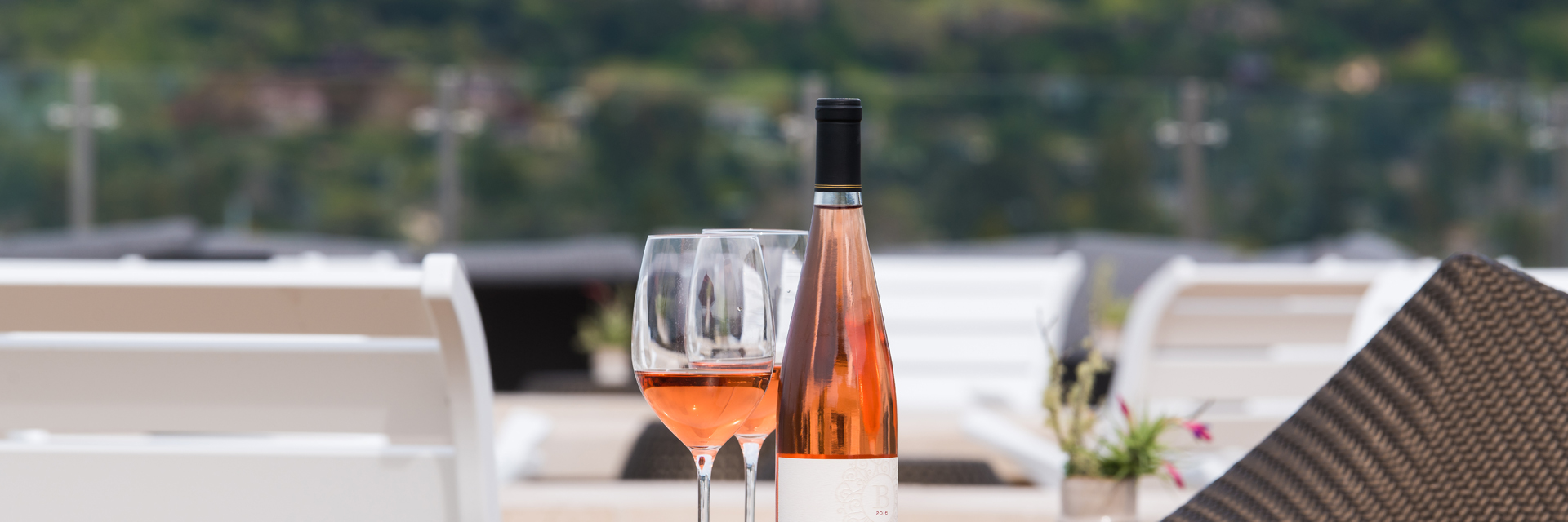 A bottle of rosé and two glasses await on an open-air rooftop, with white chairs and greenery in the background