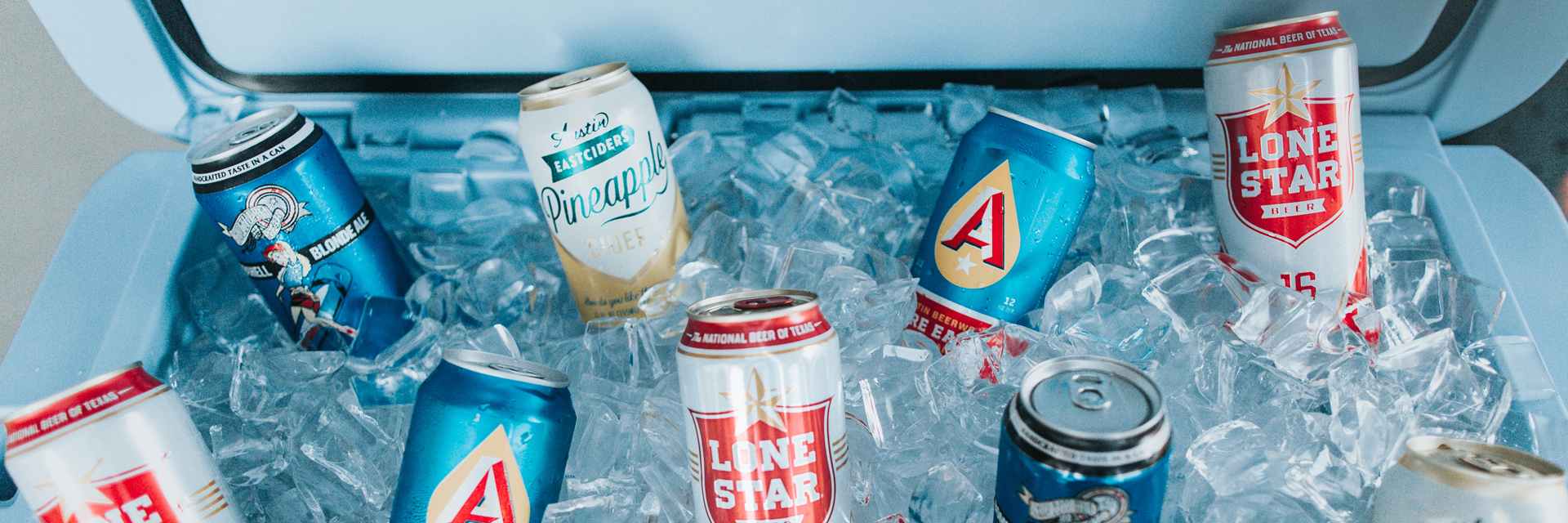 Cans of Texas beer on ice in a blue cooler