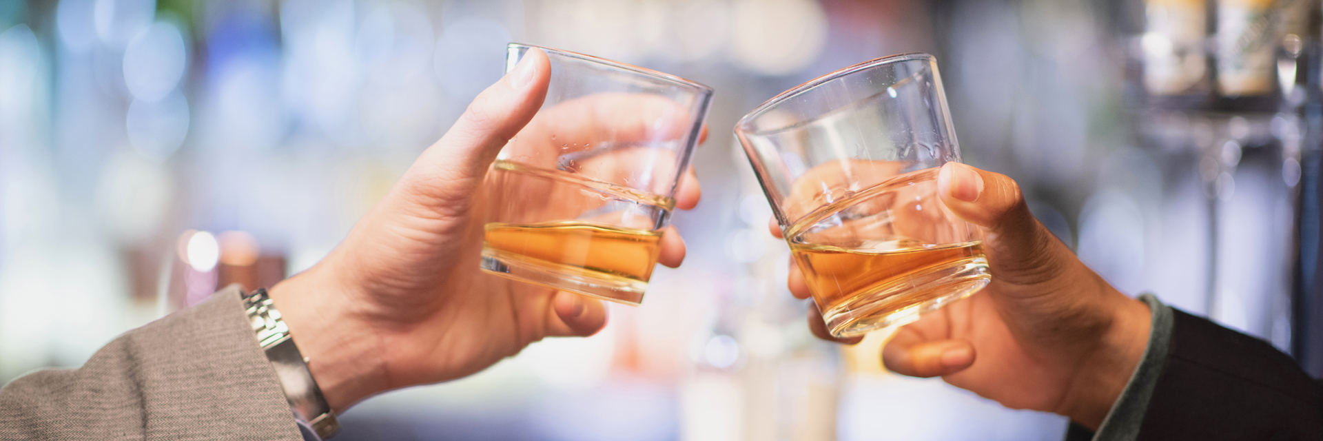A closeup of two men's hands toasting with glasses of Scotch