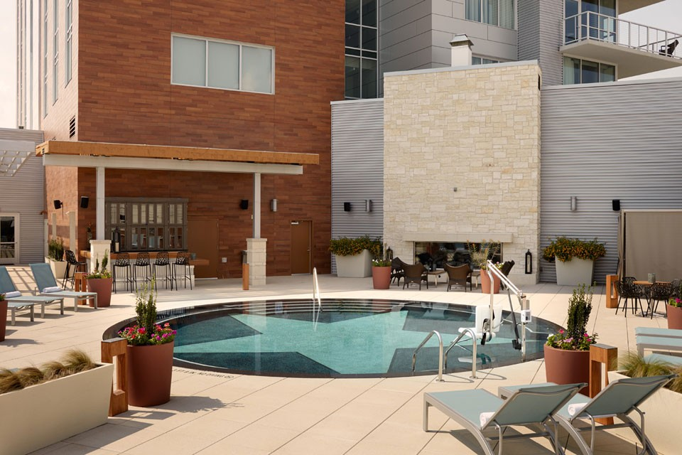 Archer Hotel Austin — Pool patio with bar, limestone fireplace and oversized TV