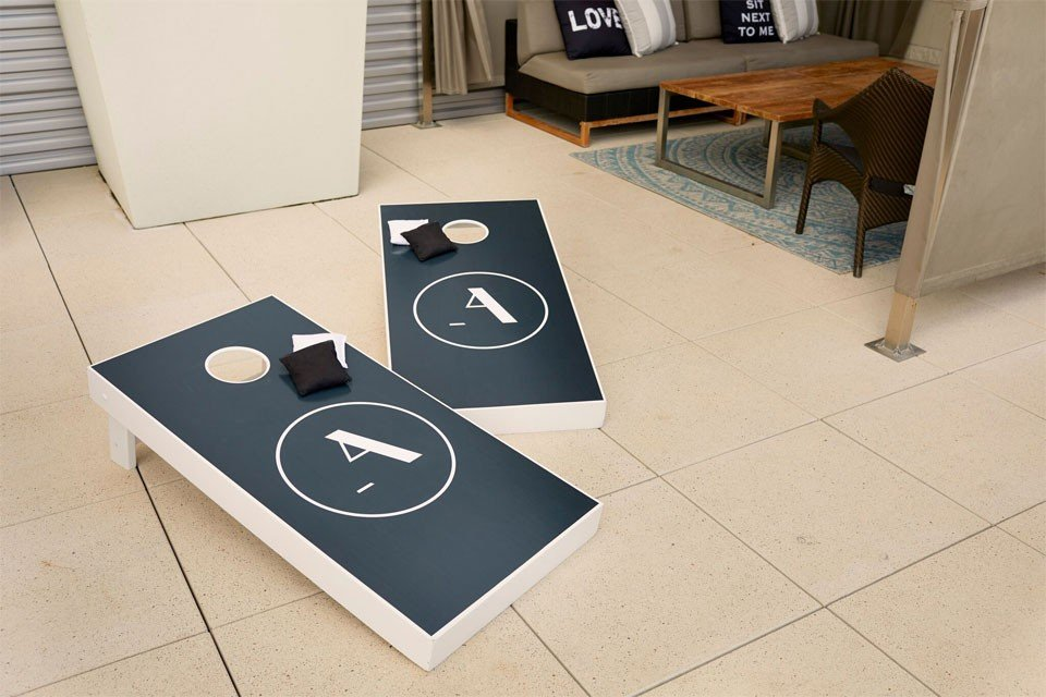 Bean bag toss game near pool patio cabana
