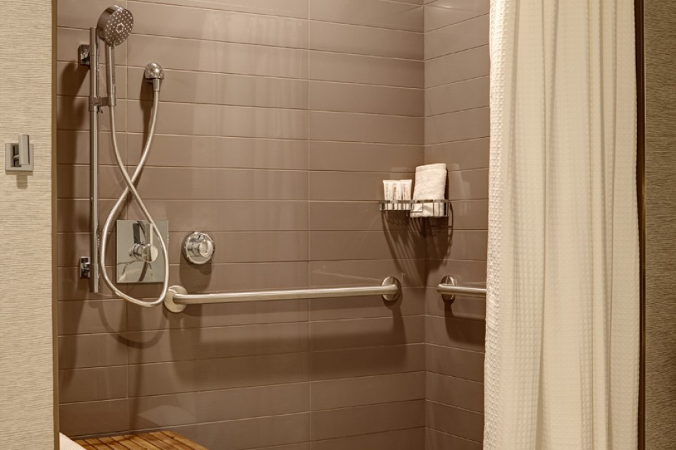 Double Queen - mobility-accessible roll-in shower with shower seat and grab bars in bathroom