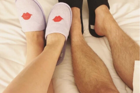 Legs of a man and a woman wearing Archer's whimsical slippers