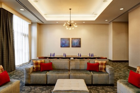 Hospitality Lounge with sofa, chairs and table with chairs in background