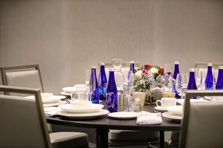 Chairs and round table set with plates, glasses, water bottles and flowers