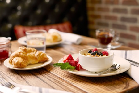 Archer Hotel Burlington — Breakfast table set with croissant, bowl of granola with fruit and coffee