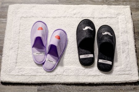 Archer's whimsical slippers with mustaches and lips on bath mat