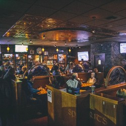 Interior of JJMahoney's, an Irish pub, with people sitting in booths and at the bar}