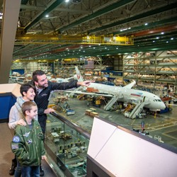Tour guide pointing out aircraft information to two boys with an aircraft in production in the background}