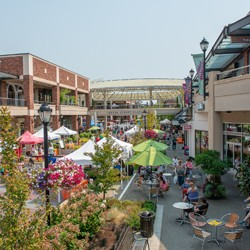 Outside aerial view of Redmond Town Center, with colorful umbrellas set up and people walking}