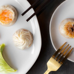 Several types of steamed dumplings on plates at Din Tai Fung}