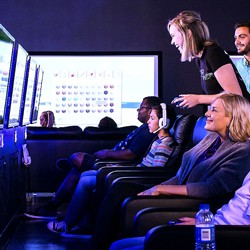 PLAYlive Nation gaming room with people in comfortable seats playing video games}