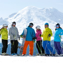 Six people in colorful ski clothes posing on Crystal Mountain with a snow-covered mountain in the background}
