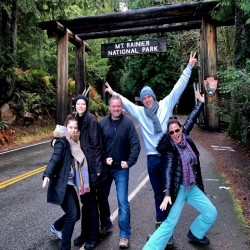 A group of people posing in front of the Mt. Rainier National Park sign}