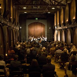Rows of people seated in a winery barrel room watching a live quartet perform}