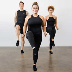 Three people in black workout clothes working out in sync}