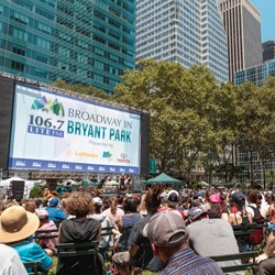 Audience seated in grassy area of Bryant Park watching a Broadway show}