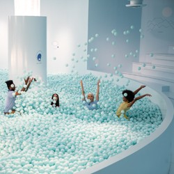 Four people playing in a large, pale blue room filled with pale blue balls}